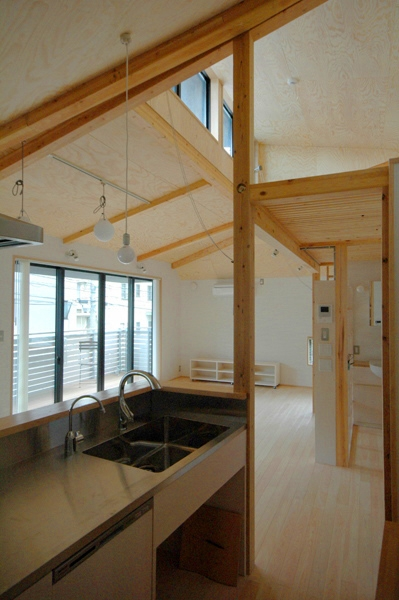 ロフトでつながる大屋根の家の部屋 オープンなキッチンからリビングを見る