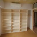 家具で仕切りをつくったマンションリノベの写真 寝室に作った壁一面の本棚と廊下の上の収納