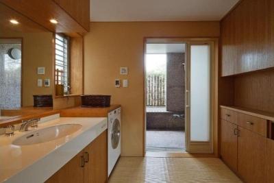 収納の多い脱衣室と石張りの浴室 (RC3階建て都市の二世帯住宅  将来を見越した高齢者への配慮)