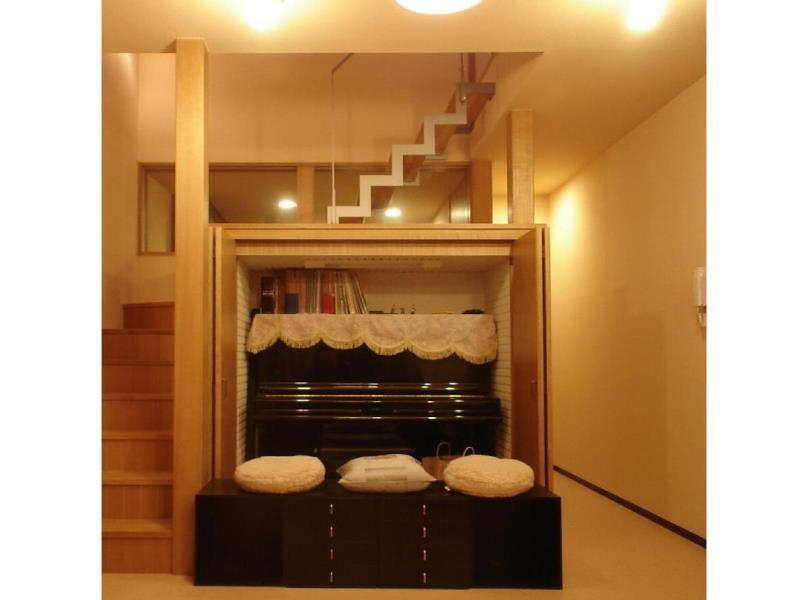 犬と共に暮らす家  室内に光を届けるリノベーションの部屋 階段/リビング側吹き抜け収納 内部にピアノが収まる