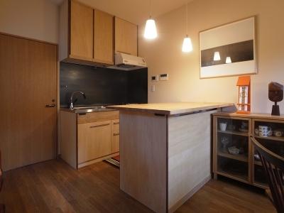 ローコストリノベーション  無機質空間から木質空間へ (キッチン/手前の作業台に冷蔵庫が収まる)