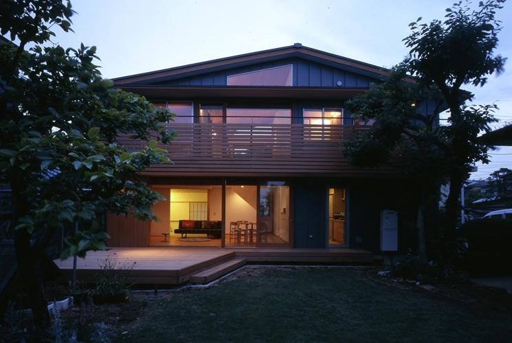 庭に開いた吹き抜けの家の写真 夕景