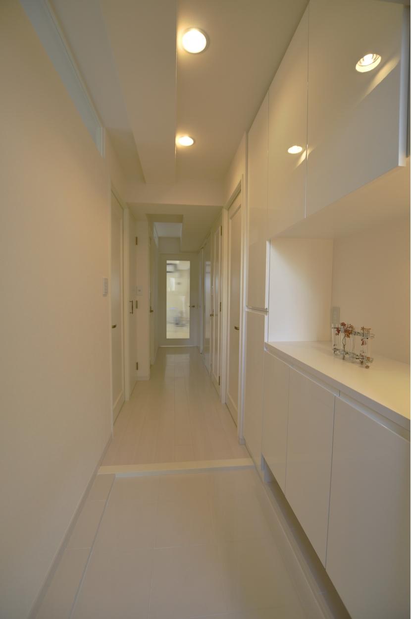 白を基調としたカフェキッチンの部屋 玄関からの廊下