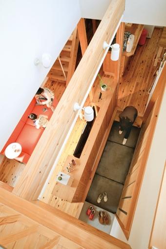 路地のある家の部屋 吹き抜け上部から玄関土間とリビングを見下ろす