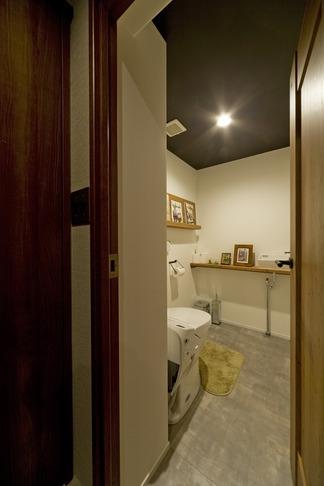 古さを活かして壁はアーチに。60年代や70年代の住まいのようなヴィンテージ風の家 (トイレ)