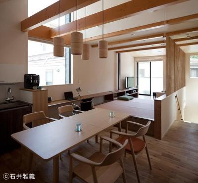 小上がりのある居間と連続するダイニング (黒の焼杉と大開口が象徴的な2世帯住宅|桜川の家)
