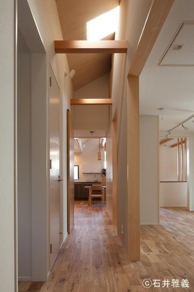 上から光が降り注ぐ中廊下 (黒の焼杉と大開口が象徴的な2世帯住宅|桜川の家)