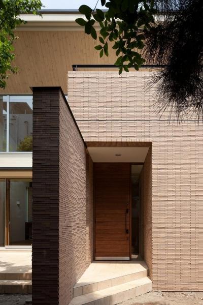 住宅密集地で陽光の恵みを受けるRC住宅|つばさの家 (壁に誘われてアプローチする玄関)