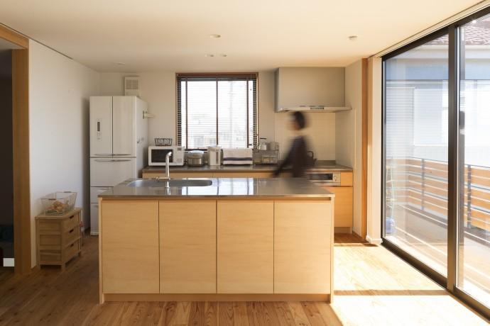 緑豊かな庭を背景に「甲板のある家」の部屋 対面式キッチン