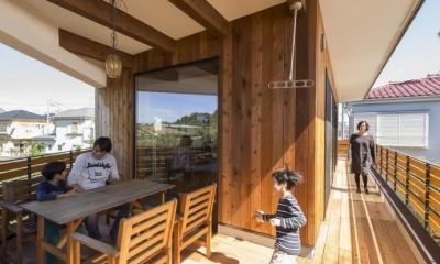 アウトドアリビングのあるバルコニー|緑豊かな庭を背景に「甲板のある家」
