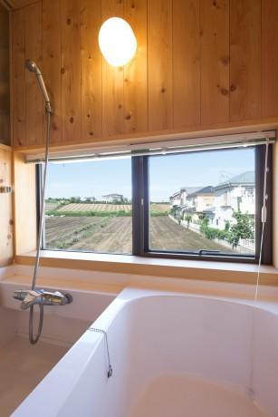 緑豊かな庭を背景に「甲板のある家」の部屋 光の差し込む浴室