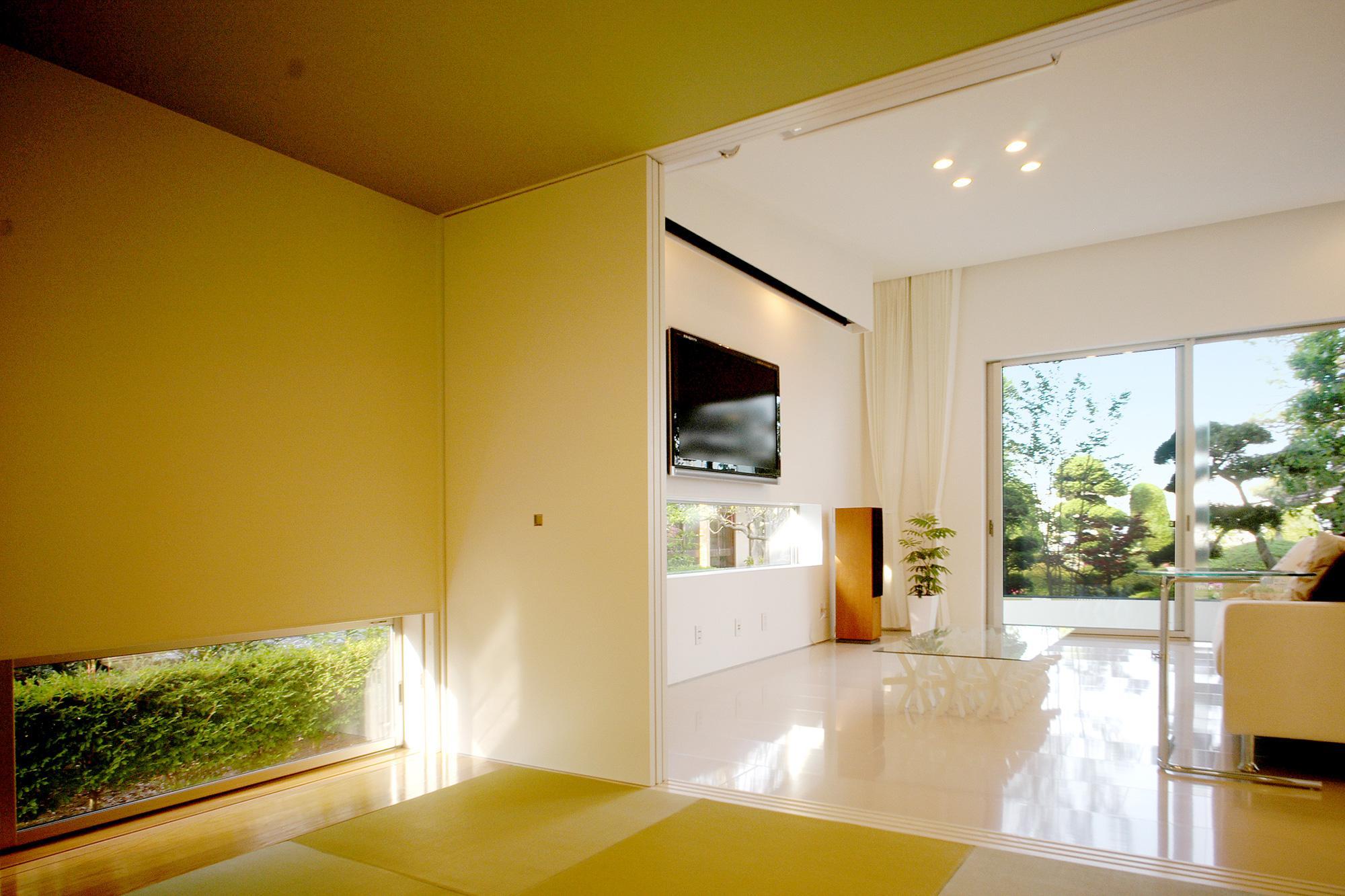 T-House <ガラスルーバーの家>の部屋 畳スペースからリビングを見る1