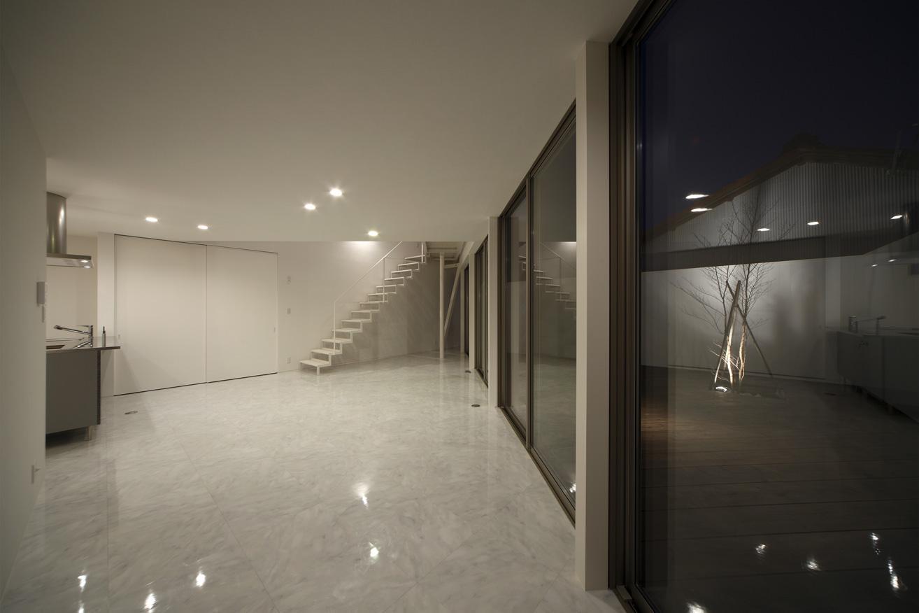 三角プランの家~斜め線で室内と室外に分かれる家~の部屋 リビングとデッキ-夜景(撮影:加斗タカオ)
