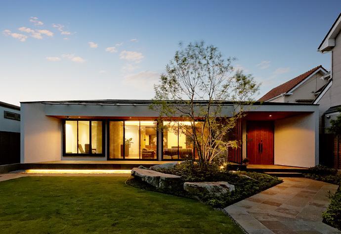 『garden house with garage』〜ガレージ・庭・ホームシアター!趣味を最大限楽しめる住宅〜の部屋 庭の緑に映える外観-夕景