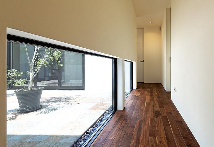 『garden house with garage』〜ガレージ・庭・ホームシアター!趣味を最大限楽しめる住宅〜 (地窓のある廊下)