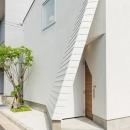 斜め壁をくぐる玄関アプローチ
