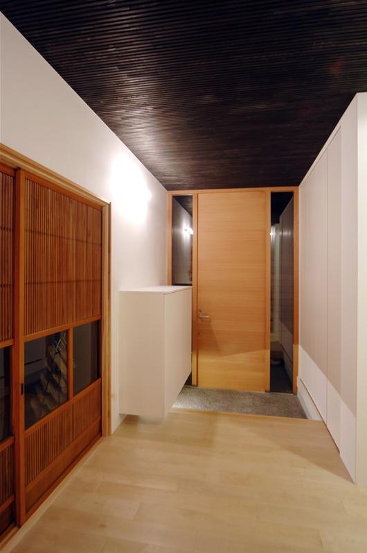 狭小土地に建つ自然素材で造る2世帯住宅 (シンプルモダンな玄関)