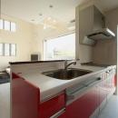 『スクエアハウス』〜大きな吹き抜けのある開放的な住まい〜の写真 赤が映える対面式キッチン