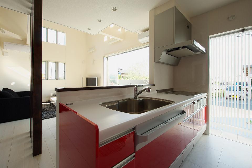 『スクエアハウス』〜大きな吹き抜けのある開放的な住まい〜の部屋 赤が映える対面式キッチン