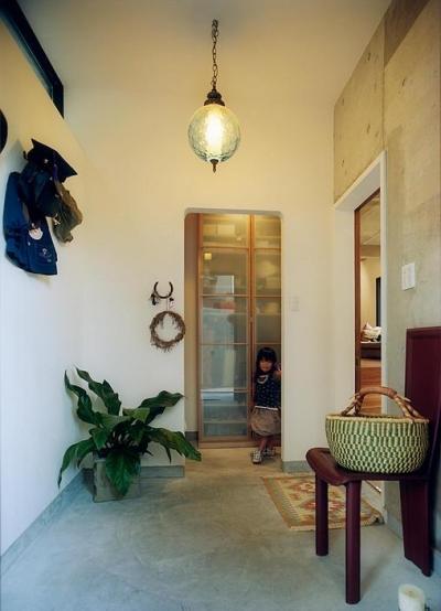 ペンダントライトが印象的な広々玄関 (『月が丘の住宅』〜荒々しくも柔らかな佇まいの住宅〜)