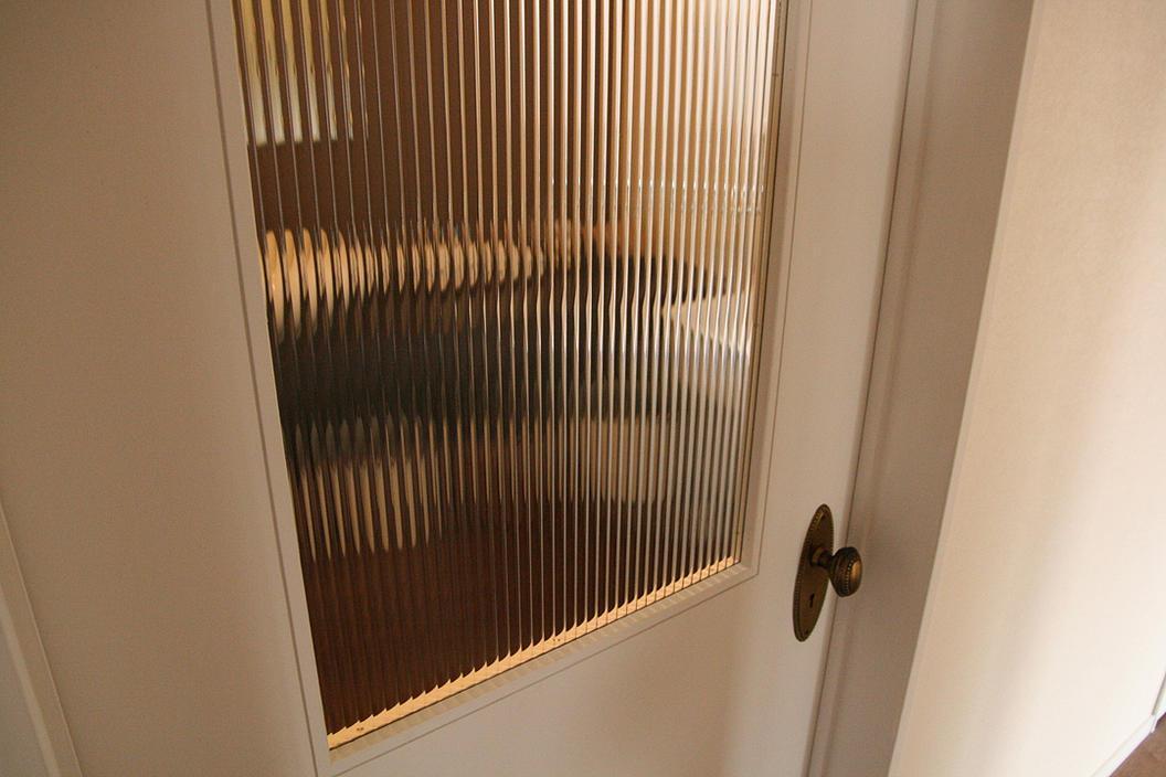 『月が丘の住宅』〜荒々しくも柔らかな佇まいの住宅〜の部屋 モールガラスのドア