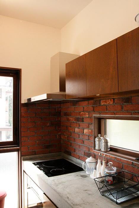 『月が丘の住宅』〜荒々しくも柔らかな佇まいの住宅〜の部屋 煉瓦壁のコンクリート製キッチン