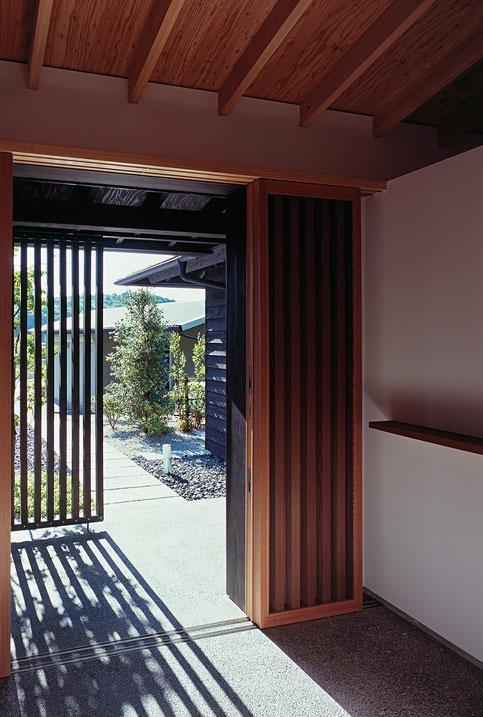 『塩河の家』〜里山の風景と暮らす家〜の部屋 玄関土間よりアプローチを見る