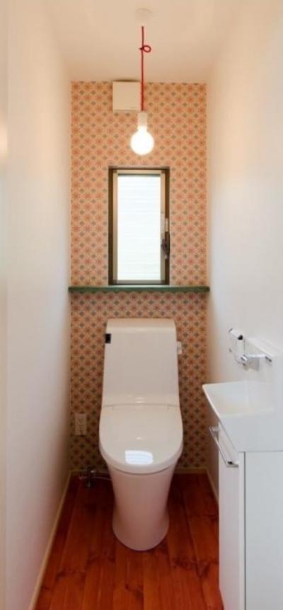 赤がポイントの可愛いトイレ空間 (『志和堀の家』スキップフロアのある家)