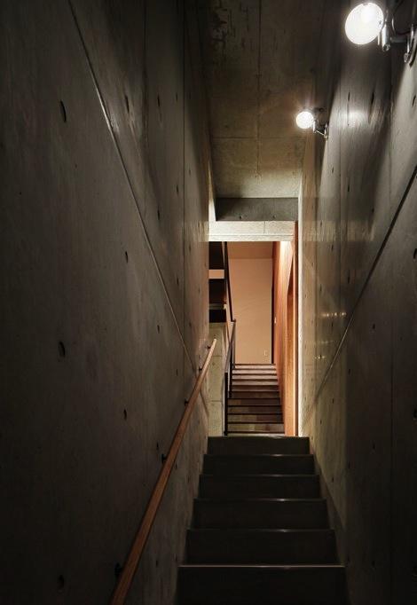 斜面に埋め込まれた家の部屋 コンクリート打ち放しの階段室