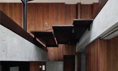 吹き抜けに面する大きな階段|斜面に埋め込まれた家