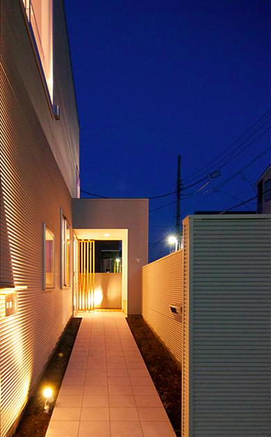 『Ka-house』家を巡る楽しさのある二世帯住宅の部屋 照明の灯りが導く玄関アプローチ