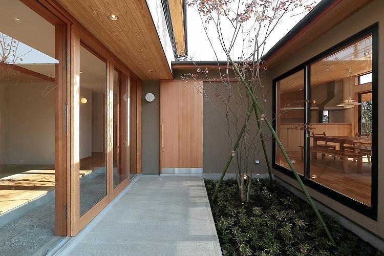『集う家』木の温もりに包まれた現代和風の家の部屋 アプローチ・中庭