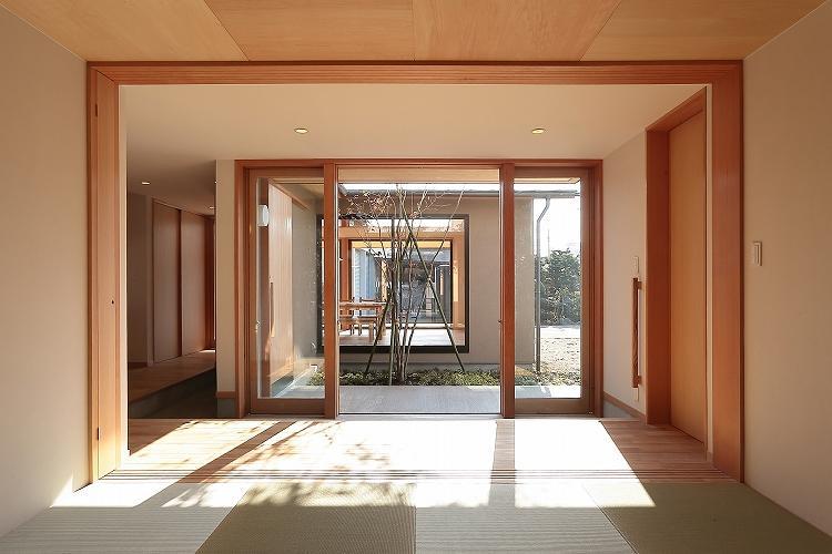 『集う家』木の温もりに包まれた現代和風の家の部屋 和室より中庭・LDKを見る