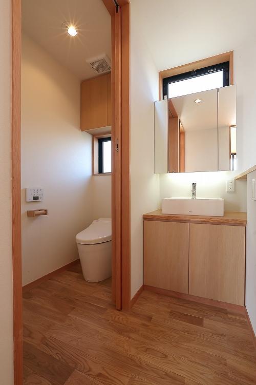 『集う家』木の温もりに包まれた現代和風の家の部屋 シンプルなトイレ空間