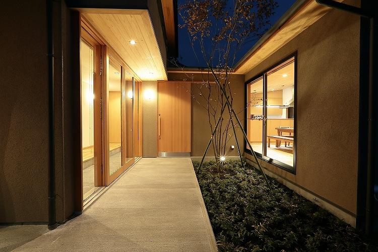 『集う家』木の温もりに包まれた現代和風の家の部屋 夜の中庭