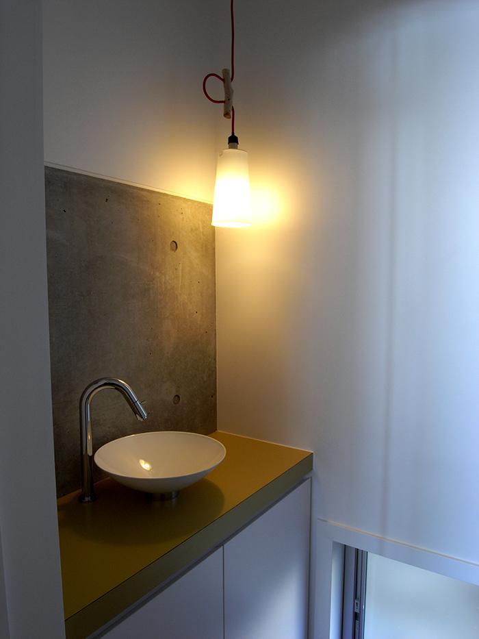 『HKH』優しい光の集まる木造2階建て住宅の写真 コンクリート現しの洗面スペース