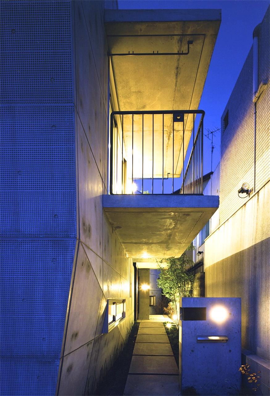 『subako』重厚感のあるコンクリート住宅の部屋 夜の玄関アプローチ