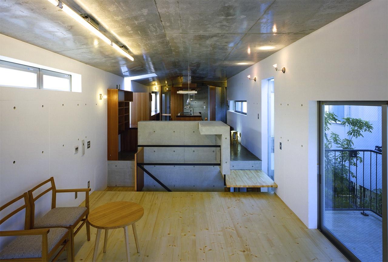 『subako』重厚感のあるコンクリート住宅の部屋 リビングよりダイニングキッチンを見る