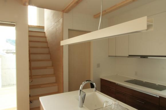 『囲みの家』プライバー・開放性を兼ね備えた住まいの部屋 キッチン側より2階に上がる階段