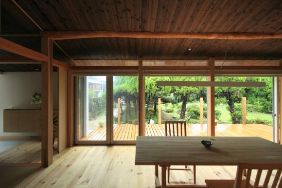 『黒天井の家』焼き杉を使用した落ち着きのある住まいの部屋 キッチンよりダイニング・テラスを見る