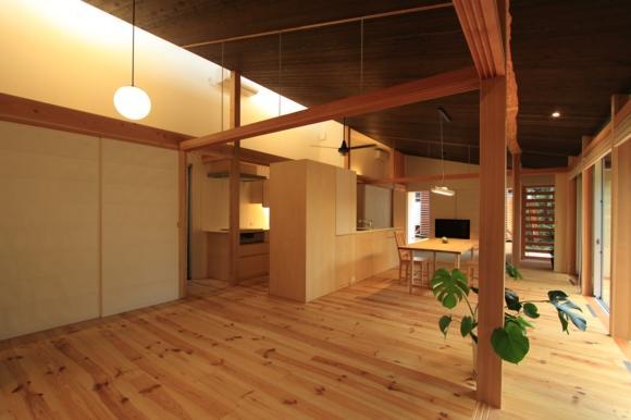 『黒天井の家』焼き杉を使用した落ち着きのある住まいの部屋 リビングよりダイニングキッチンを見る