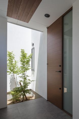 『高松の家』中庭を囲む平屋住宅の部屋 玄関脇には緑を