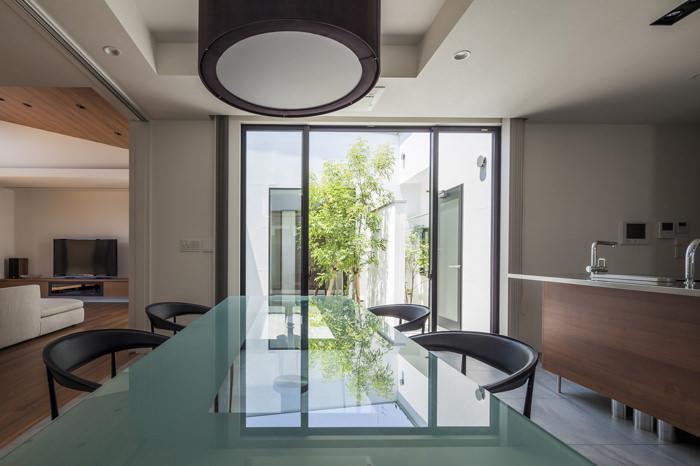 『高松の家』中庭を囲む平屋住宅の部屋 広さを演出するガラステーブルのダイニング