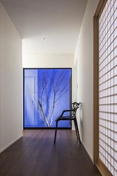 廊下・ライトアップされた坪庭 (『松前町の家』おおらかな葺き下ろし屋根の家)