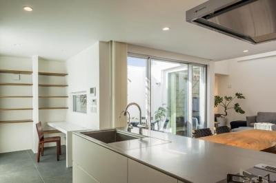 明るい対面式キッチン (『道後のコートハウス』共に成長し、共に時を刻む住まい)