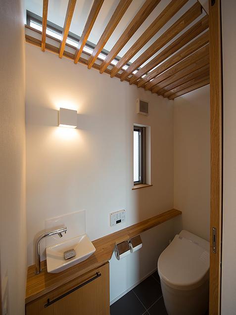 『higashitakamatsu』木の温もり感じるモダンな住まい (木製ルーバー天井のトイレ)