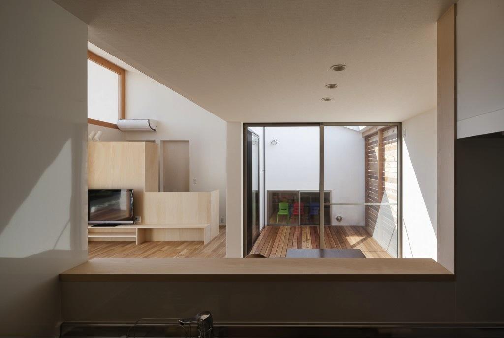 『5つのテラスの家』光と風を楽しむ住まいの部屋 キッチンよりダイニング脇テラスを見る