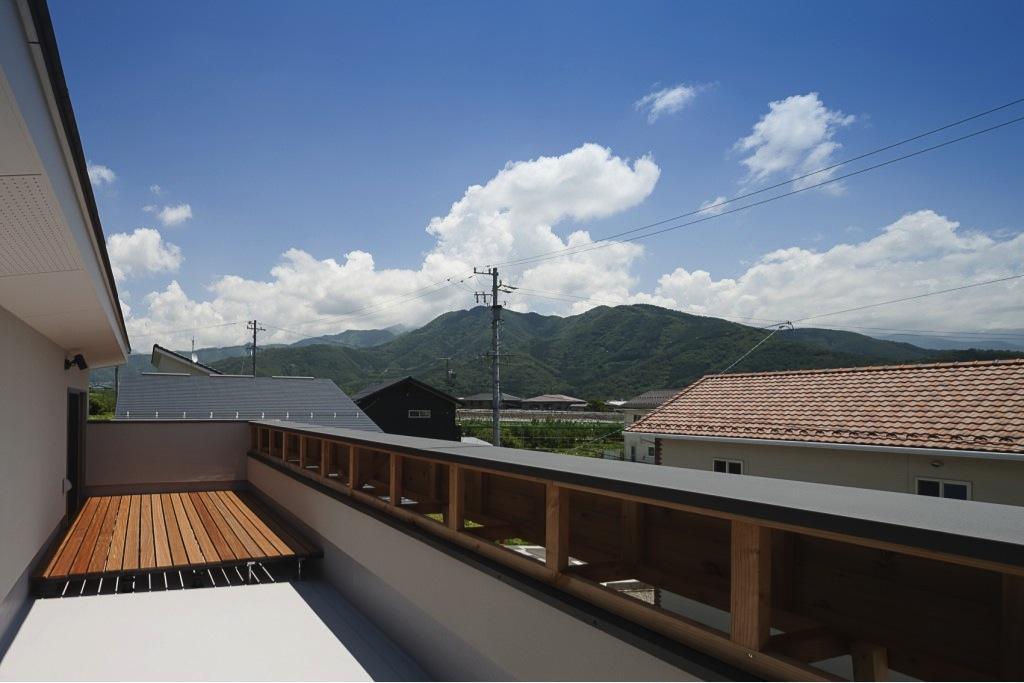 『須坂の家』大きな吹抜けと大きなテラスの住まいの部屋 山々を臨む屋上テラス
