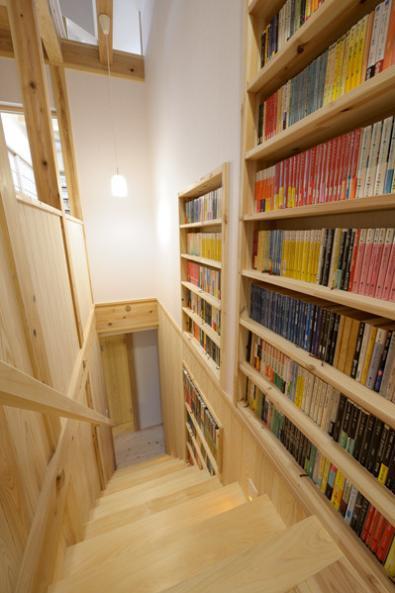 『B/storage』本がたくさんあるシンプルな木の家の写真 壁一面本棚の階段
