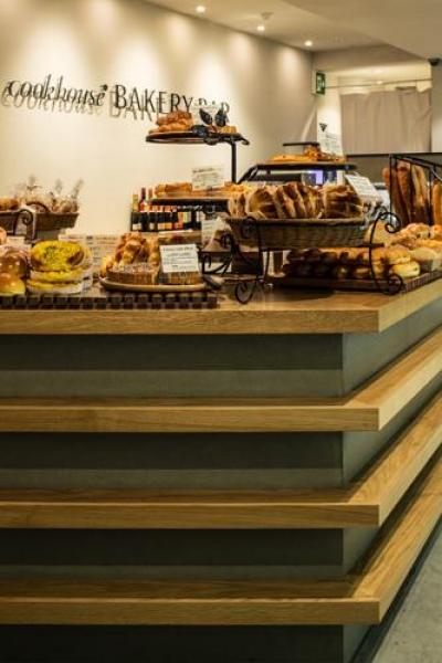 『cookhouse BAKERY BAR』カウンターのデザイン (美味しそうなパンが並ぶカウンター)